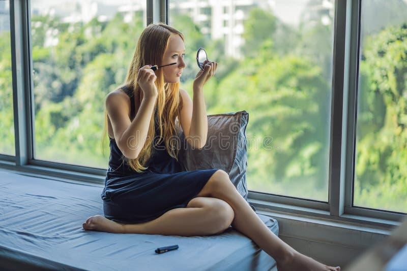 Junge Frau wendet Make-upfront des Fensters in der Sch?nheitsstudiowohnung an Berufsmake-uphaaranreden haut stockbilder