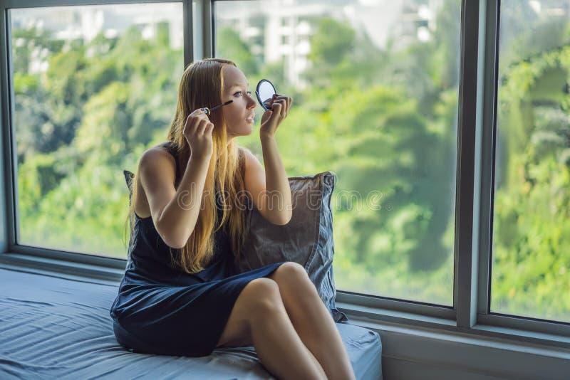 Junge Frau wendet Make-upfront des Fensters in der Sch?nheitsstudiowohnung an Berufsmake-uphaaranreden haut lizenzfreies stockbild
