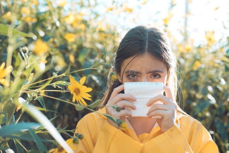 Junge Frau wird niesen Das Mädchen leidet unter Pollenallergie während des Blühens und benutzt Servietten Hübsche Frau erhalten stockfoto