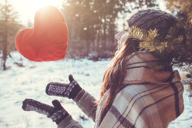 Junge Frau wirft ein rotes Kissenherz im Winterwald lizenzfreies stockbild