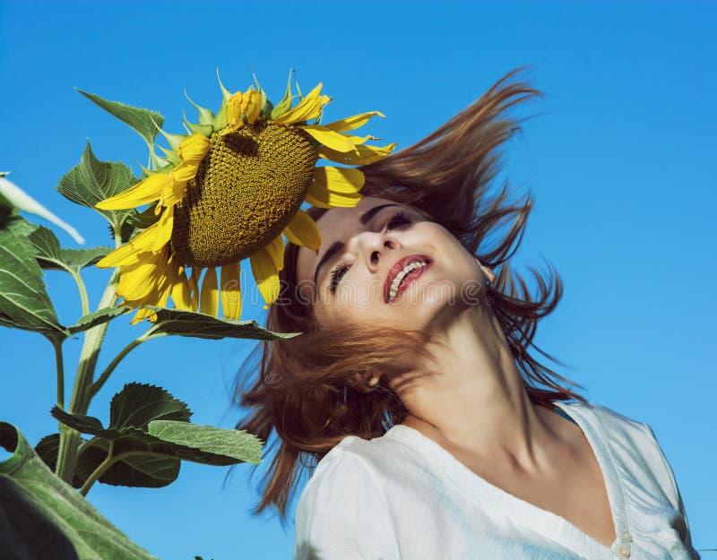 Junge Frau wirft ihr Haar durch die Sonnenblume auf dem Gebiet stockbild