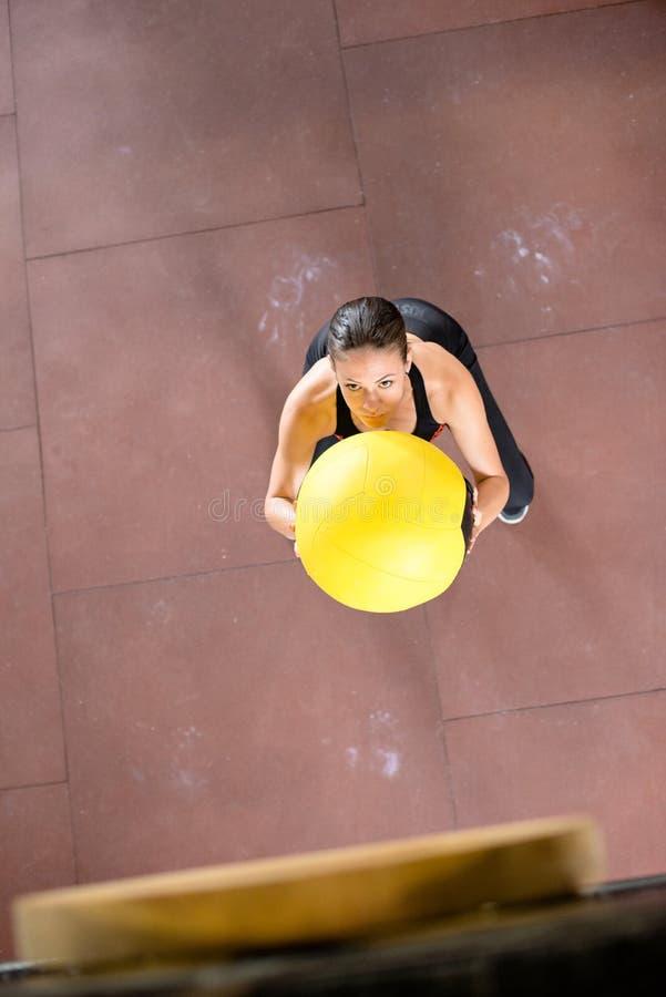 Junge Frau wirft Medizinball lizenzfreie stockbilder