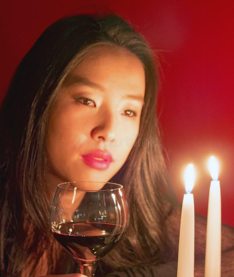 Junge Frau wirft mit dem Weinglas auf, das Kerzen anstarrt stockfotografie