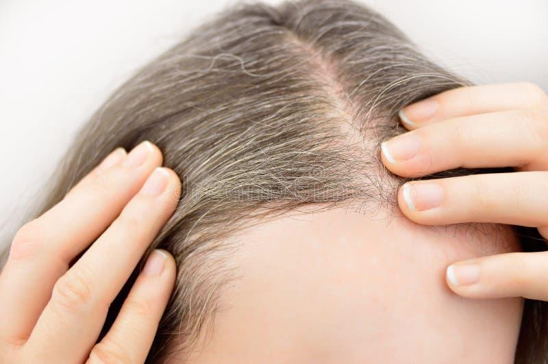 Junge Frau zeigt ihr graues Haar lizenzfreie stockbilder
