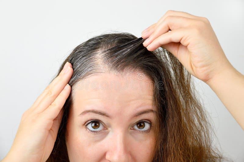 Junge Frau zeigt ihr graues Haar lizenzfreie stockfotos