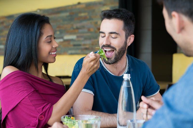 Junge Frau zieht dem Mann Salat ein lizenzfreie stockfotos