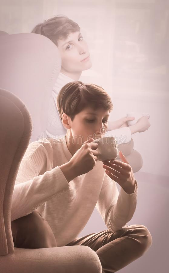 Junge Frau zu Hause, die auf modernem Stuhl vor dem Fenster sich entspannt in ihrem Wohnzimmer sitzt stockfotos