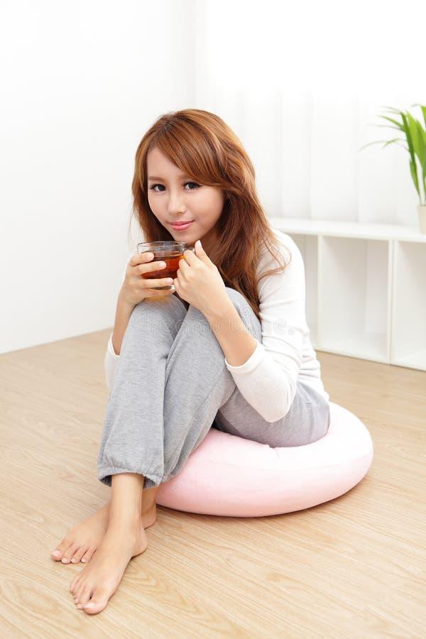 Junge Frau zu Hause, die an Tee nippt stockbilder