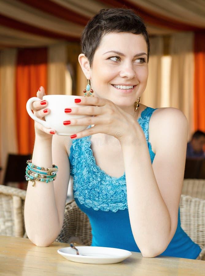 Junge Frau zu Hause, die an Tee von einem Cup nippt lizenzfreies stockfoto
