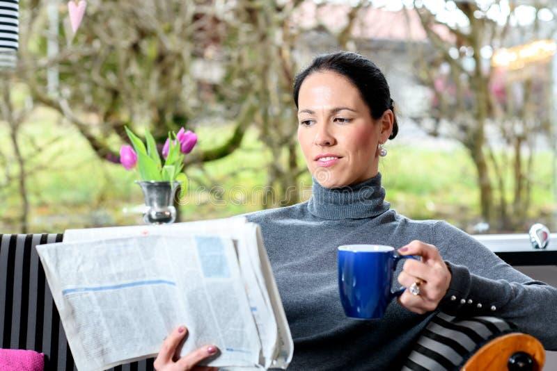Junge Frau zu Hause mit Schale coffeee Entspannungsund Ablesenn lizenzfreies stockfoto