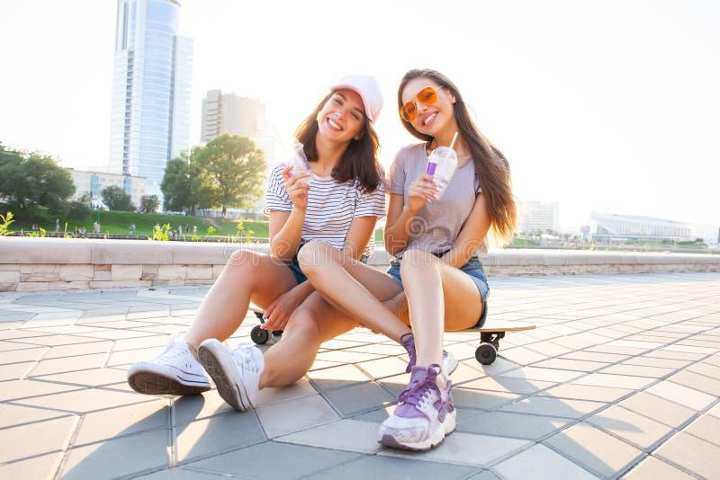 Junge Frau zwei, die auf dem Skateboard-glücklichen Lächeln sitzt Spielerische Freunde genießen sonnigen Tag Städtisches im Freie lizenzfreie stockfotos