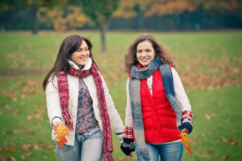 Junge Frau zwei, die in Herbstpark geht