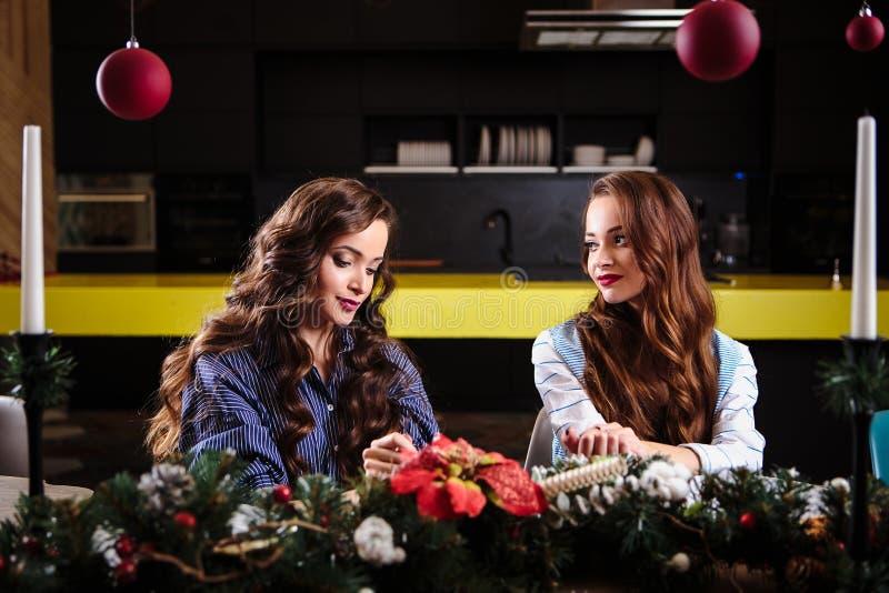Junge Frauen der hübschen Zwillinge zusammen in einem Küchenraum, zufällige Hauptart, Dekorationen des neuen Jahres Weihnachts stockbilder
