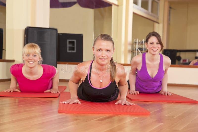 Junge Frauen, die Übungen ausdehnend in der Gymnastik durchführen lizenzfreie stockfotografie