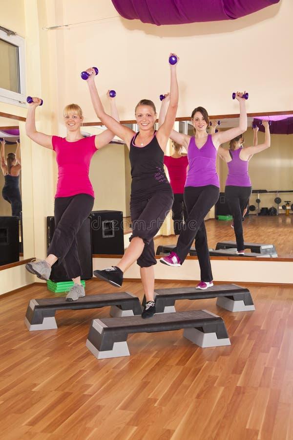 Junge Frauen, die Aerobics in der Gymnastik ausüben stockfotos