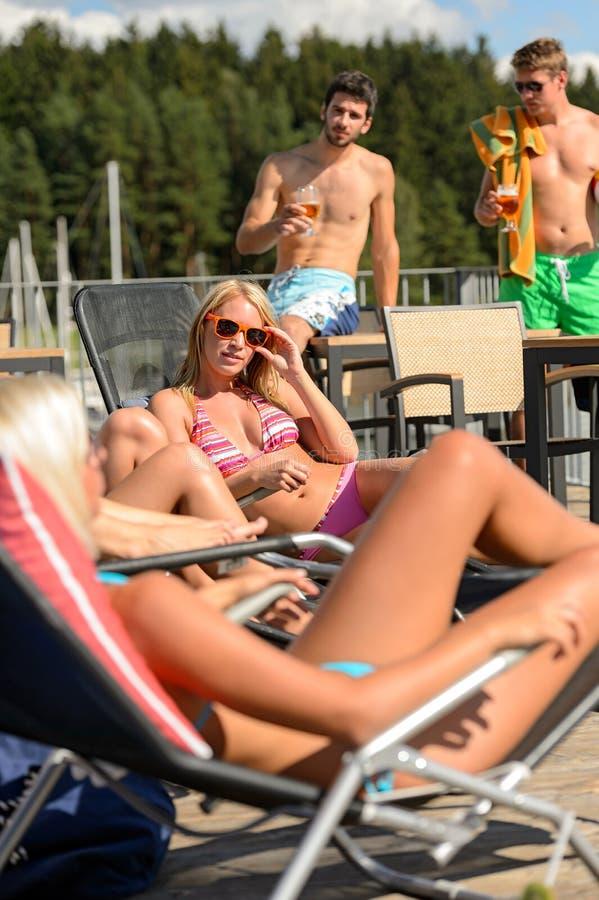 Frauen, die auf deckchair Kerlen trinken Bier ein Sonnenbad nehmen lizenzfreie stockbilder