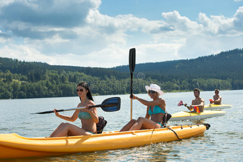 Junge Studenten, die im Sonnenschein kayaking sind stockfotos