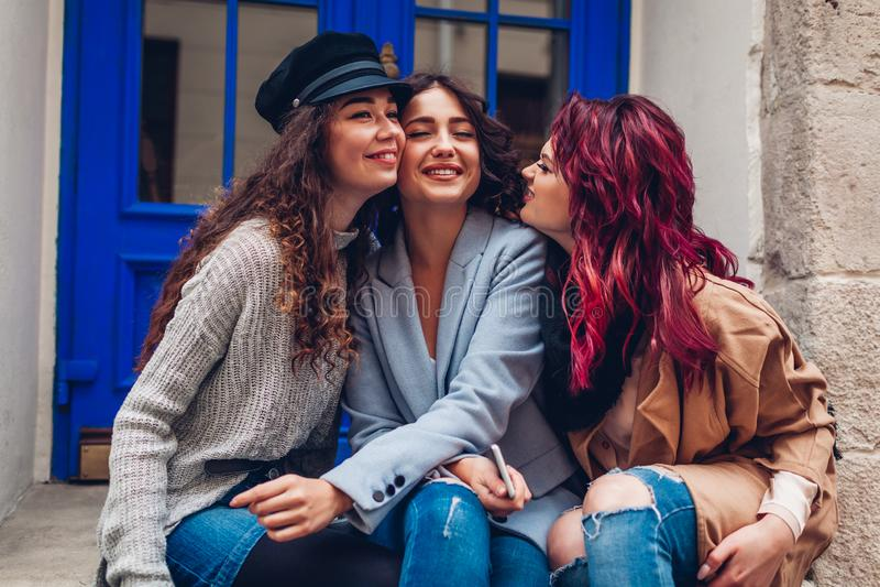 Junge Frauen, die auf Stadtstra?e umarmen und lachen Beste Freunde, die gute Zeit zusammen haben lizenzfreie stockfotografie