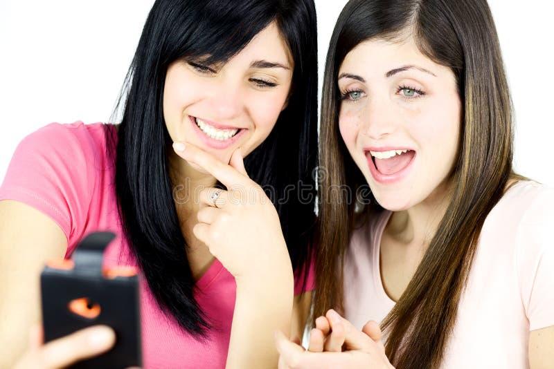 Junge Frauen, die Bilder auf dem glücklichen Lachen des Handys schauen lizenzfreies stockbild