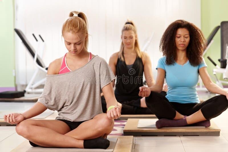 Junge Frauen, die an der Turnhalle sich entspannen lizenzfreies stockfoto
