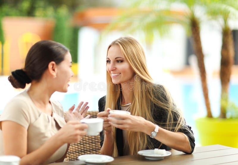 Junge Frauen, die draußen Kaffee in einem Café trinken stockfoto