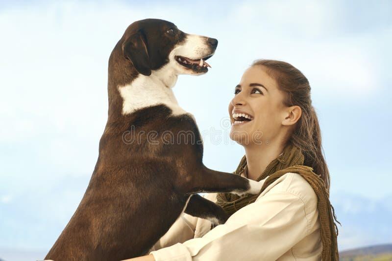 Junge Frauen, die draußen mit Hund spielen stockfotos