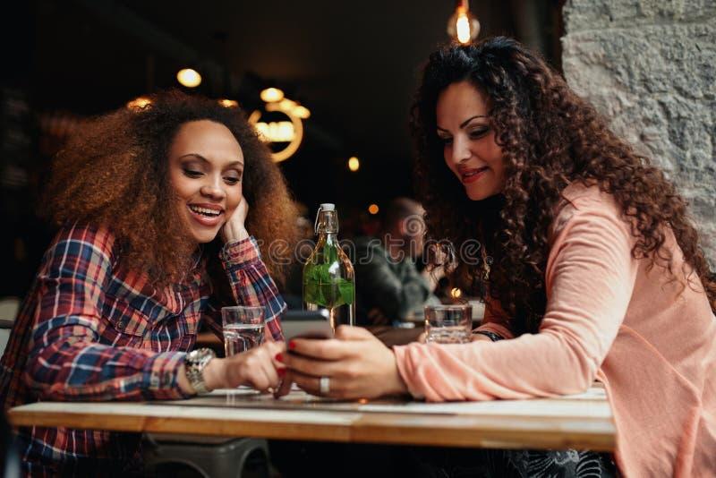 Junge Frauen, die an einem Café unter Verwendung des Handys sitzen stockfotografie