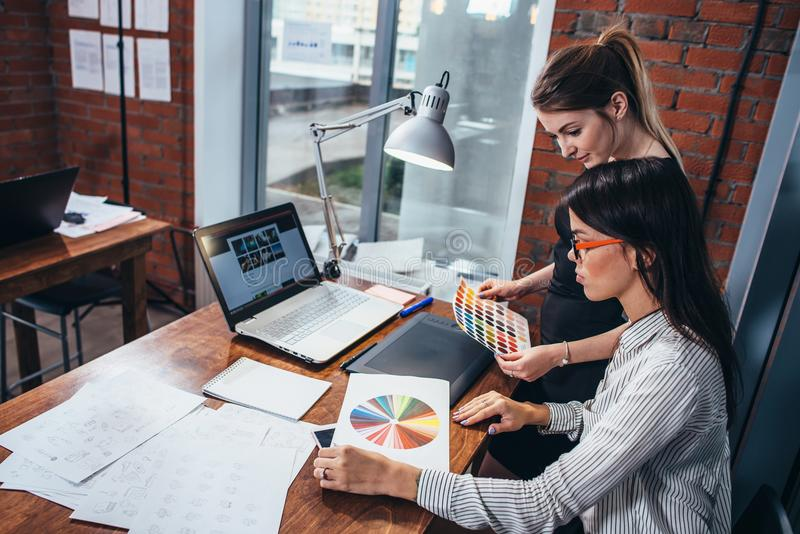 Junge Frauen, die an einem neuen Webdesign unter Verwendung der Farbmuster und den Skizzen sitzen am Schreibtisch im modernen Bür stockfotografie