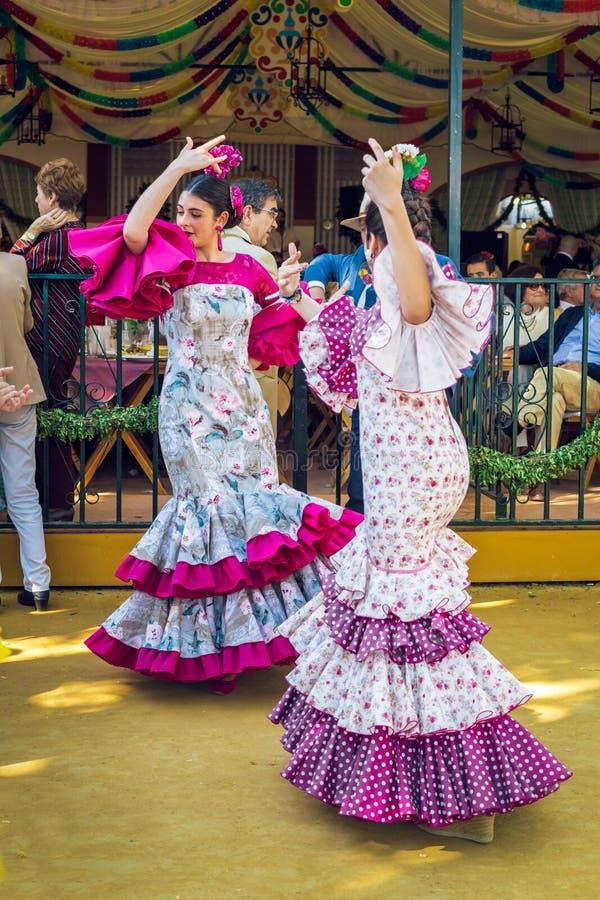 Junge Frauen, die Flamencokleider tragen und 'Sevillanas bei April Fair, Sevillas angemessene Feria de Sevilla tanzen stockbild