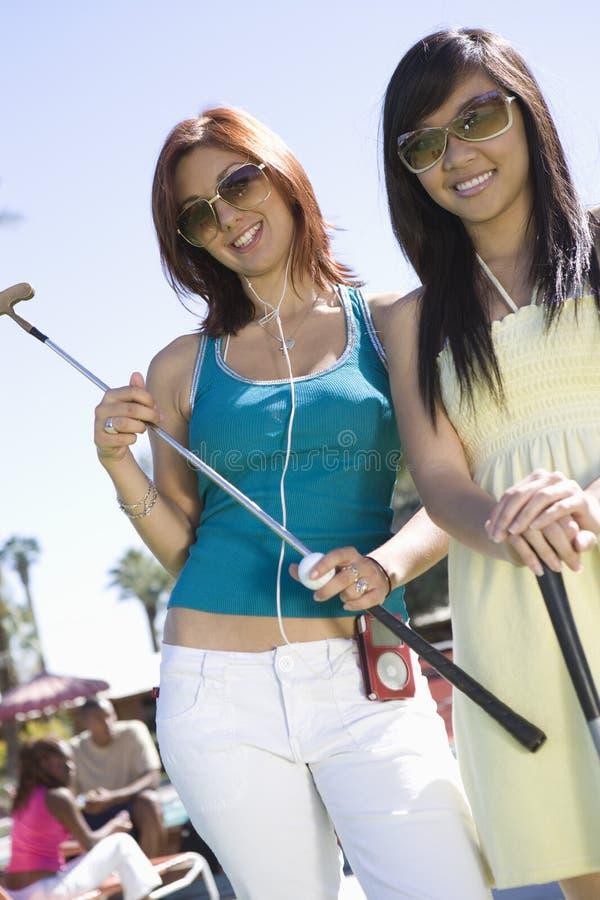 Junge Frauen, die Golfclubs halten stockfoto