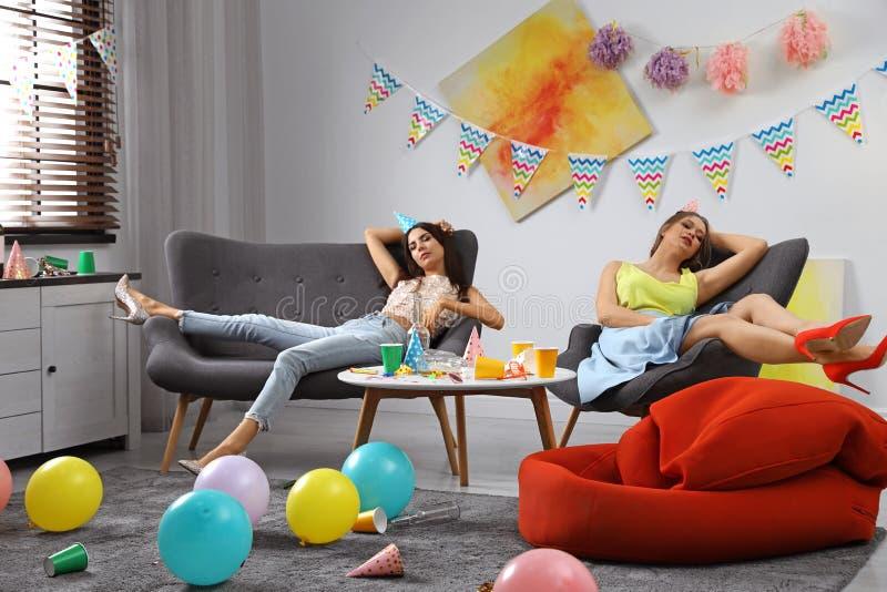 Junge Frauen, die im unordentlichen Raum schlafen lizenzfreie stockfotos