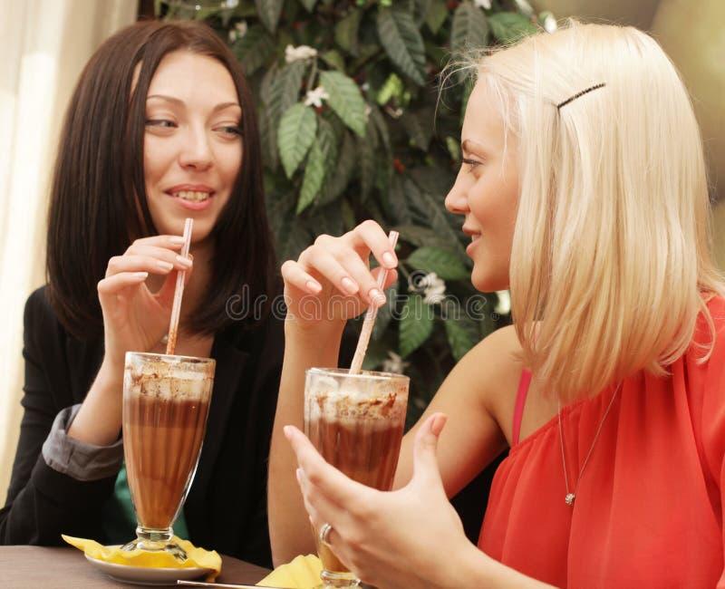 Junge Frauen, die Kaffeepause zusammen haben lizenzfreie stockfotos