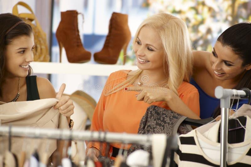 Junge Frauen, die am Kleidungsspeicher kaufen stockbild