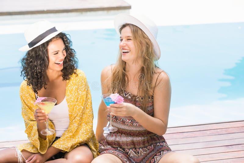 Junge Frauen, die Martini nahe Pool haben lizenzfreie stockfotos