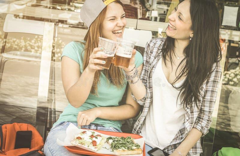 Junge Frauen, die Pizza essen und Bier am Barrestaurant trinken stockfotografie