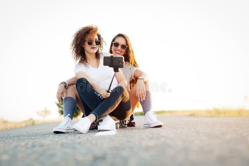 Junge Frauen, die zusammen auf longboard in der Straße nimmt selfie stationieren lizenzfreies stockbild