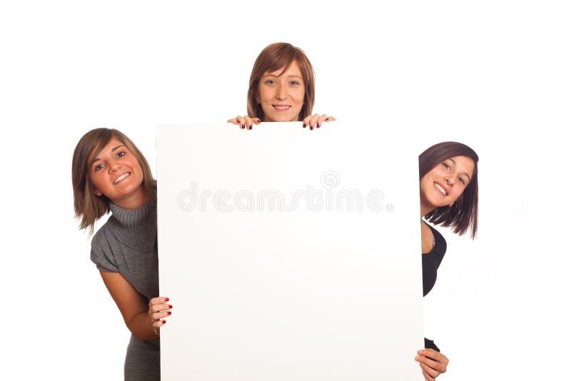 Junge Frauen halten unbelegtes Zeichen an lizenzfreie stockbilder