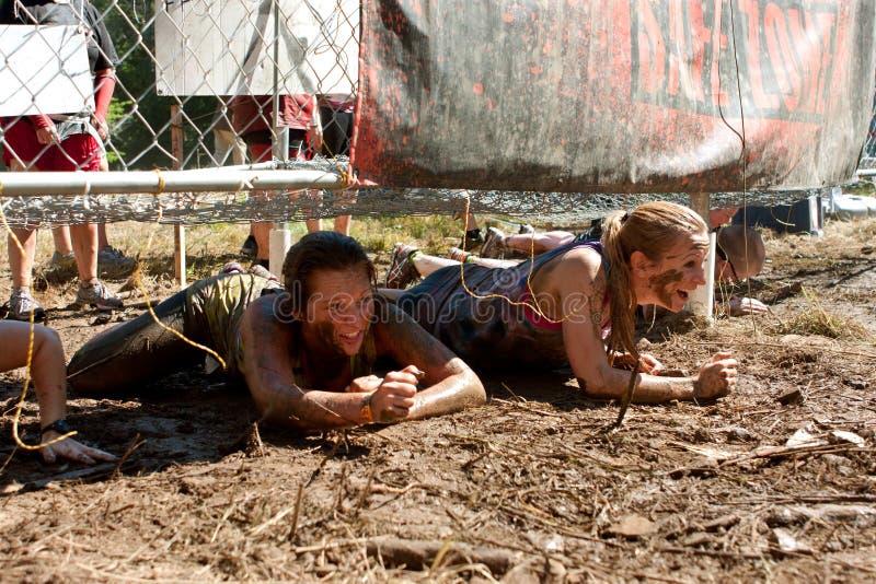 Junge Frauen kriechen unter elektrifiziertes Hindernis-Rennen Zaun-In 5K lizenzfreie stockfotos