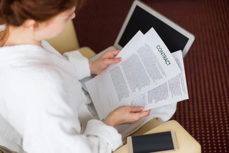 Junge Frauen-Leseverträge während der Geschäftsreise lizenzfreie stockfotografie