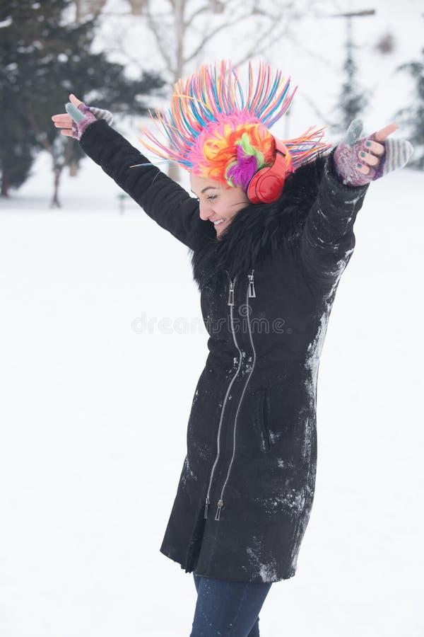 Junge Frauen mit bunter Perücke des Clowns und Kopfhörer am Schneetag lizenzfreie stockfotografie