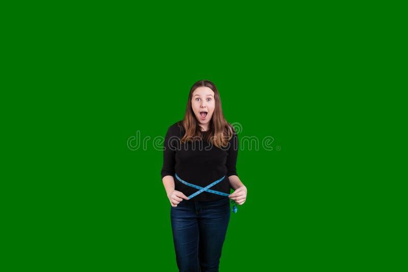 Junge Frauen mit einem aufgeregten Ausdruck, der ihre Taille mit blauem messendem Band misst stockbild