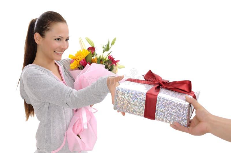 Junge Frauen mit Geschenk und Blumen lizenzfreies stockbild