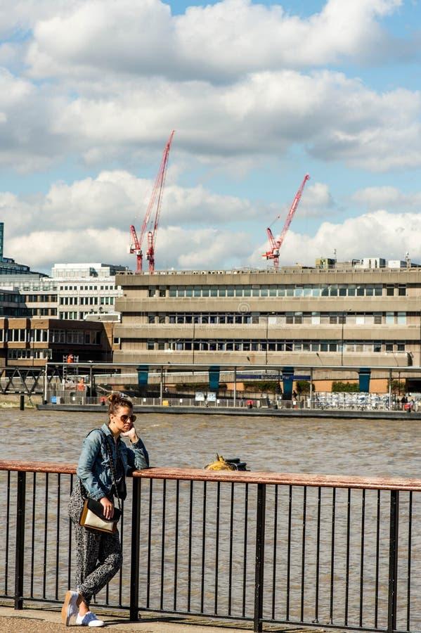 Junge Frauen-Tourist, der gebohrt oder auf einem Zaun Overlooking die Themse tief lehnend verloren schaut lizenzfreies stockfoto