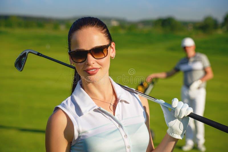 Junge Frauen und Männer, die Golf spielen stockfotografie