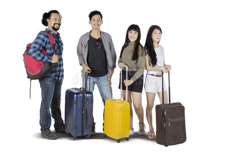 Junge Frauen und junge Männer im Besitz von Koffer lizenzfreies stockbild
