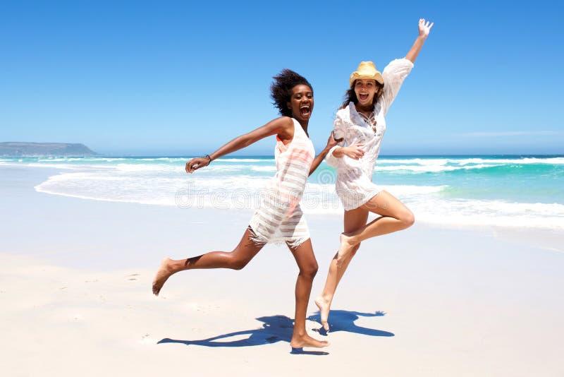 Junge Freunde, die auf dem Strand lachen und laufen lizenzfreies stockbild