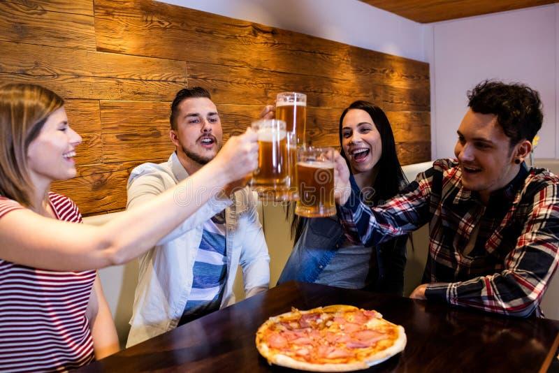 Junge Freunde, die Bier rösten stockfotografie
