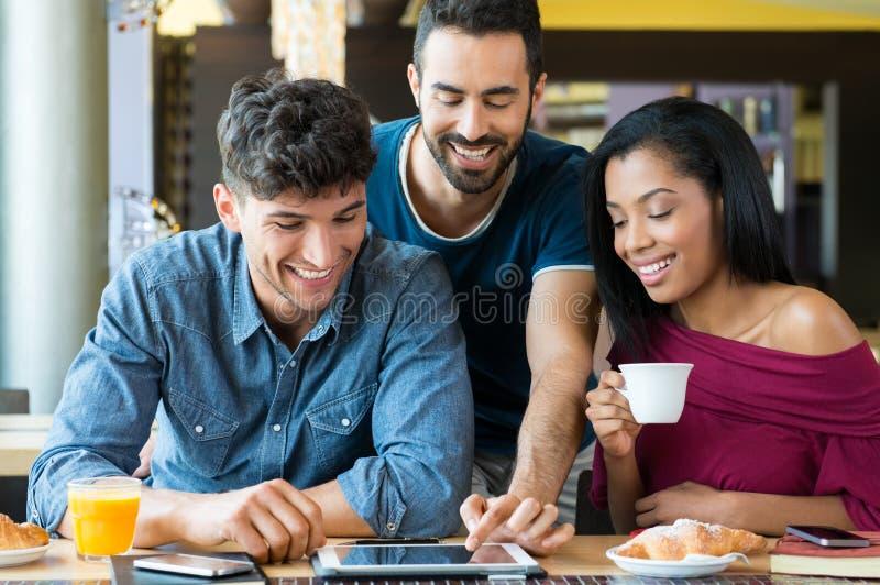 Junge Freunde, die digitale Tablette verwenden lizenzfreies stockbild