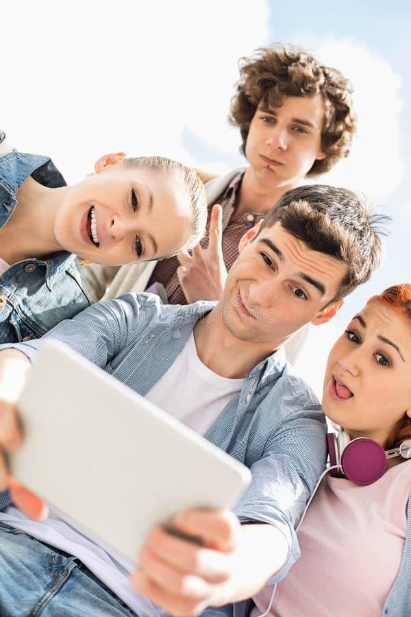 Junge Freunde, die durch digitale Tablette am Universitätsgelände sich fotografieren lizenzfreie stockfotos