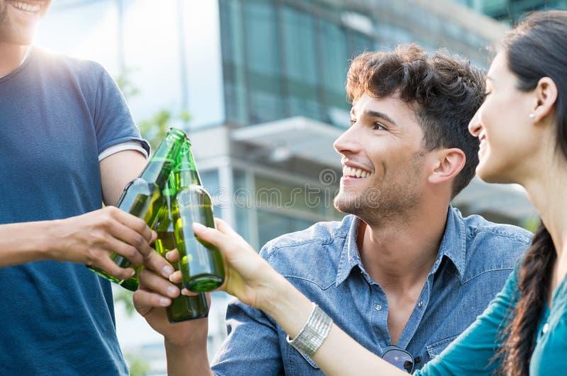 Junge Freunde, die mit Bier rösten stockfotos